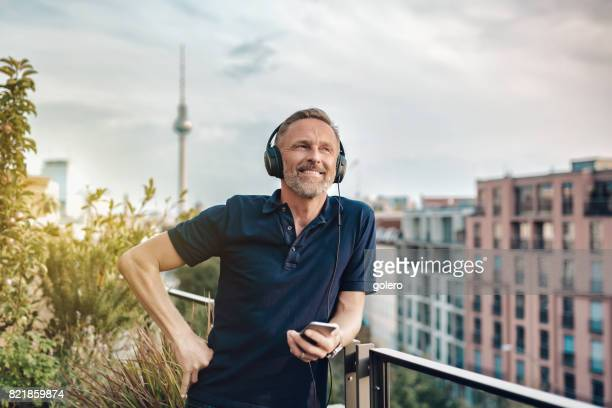handsome bearded midaged man with headphones at balcony in Berlin