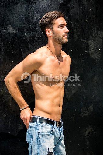 794f74236afe14 Schöner bärtiger Nackter Oberkörper junger Mann stehend gegen schwarze Wand    Stock-Foto
