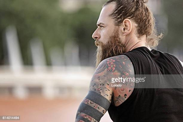 Handsome bearded tattooed man sitting alone in urban setting