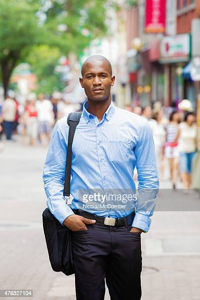 Handsome Black bald office worker street portrait with laptop bag