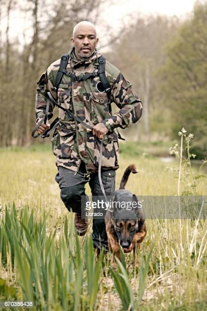 Handsome black middle aged man training with attack dog