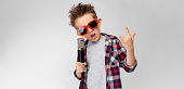 Charming happy child on gray background. The boy's hair is up. The boy has a hairstyle. The boy in round sunglasses. A handsome boy with a red hair color. The boy holds a microphone in his hand.