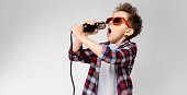 Charming happy child on gray background. The boy's hair is up. The boy has a hairstyle. The boy in round sunglasses. A handsome boy with a red hair color. The boy sings into the microphone.