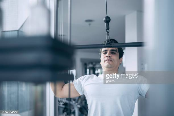 handsome brazilian athlete pulling weitght at exercise machine