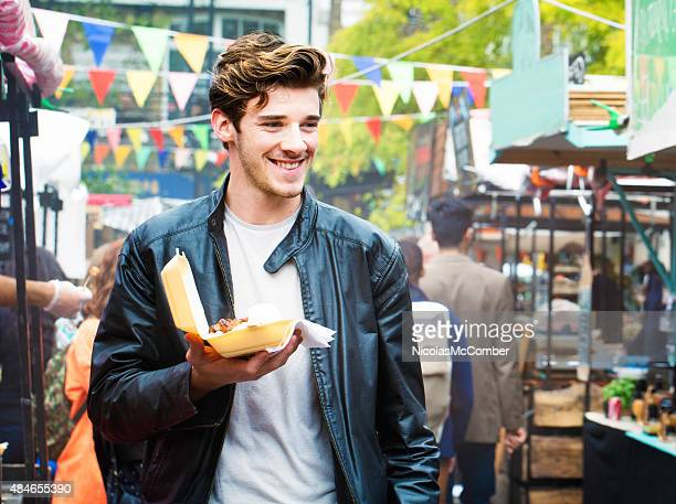 Handsome British man walks through fair market with street food