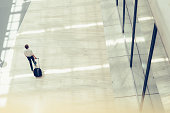 Handsome business holding a trolley and walking in a modern building seen from above
