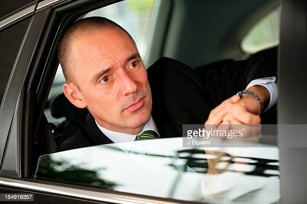 Gut aussehend business-Mann, die Zeit im hektischen Auto