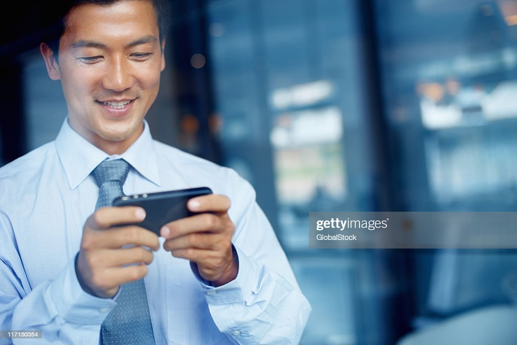 Handsome business man text messaging during office break : Stock Photo