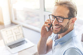 Handsome young businessman in casual clothes and eyeglasses is talking on the mobile phone, looking at camera and smiling while working