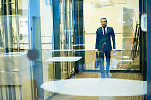 Full length portrait of handsome young businessman walking in hall of modern office building, shot from behind glass wall, copy space