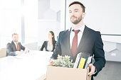 Waist up portrait of handsome businessman holding box of personal belongings  leaving office after quitting job, copy space