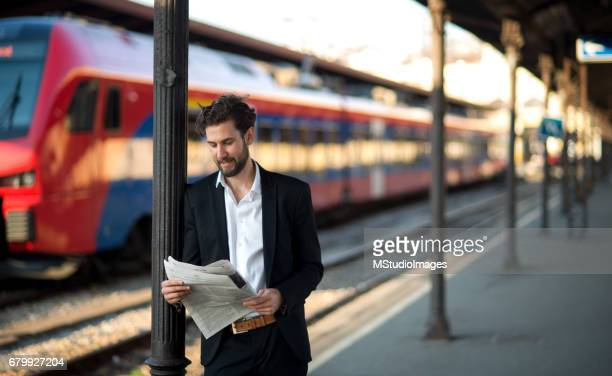 Handsome businessman reading newspapers