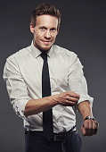 Handsome businessman rolling up his shirt sleeves while looking at the camera with a friendly smile, grey background