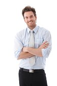 'Handsome young businessman standing arms crossed, smiling confidently...'