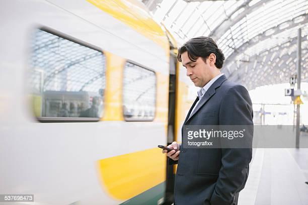 Bel homme d'affaires debout et attendre sur une plate-forme de la station de train