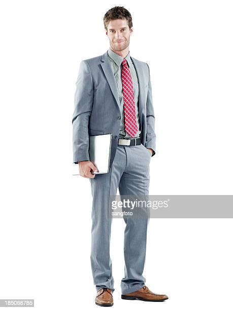 Handsome businessman standing smiling holding a laptop