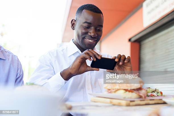 Gut aussehend Geschäftsmann nimmt ein Foto von seiner Mittagessen