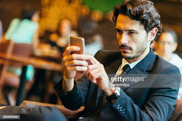 handsome businessman typing text message while relaxing in the bar