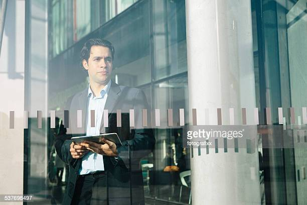 handsome Businessman with digital tablet stands behind Window, looks away