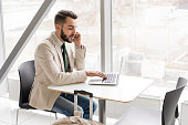Portrait of handsome bearded businessman speaking by phone and using laptop sitting at table against window in modern office building, copy space
