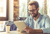 Handsome businessman in casual wear and eyeglasses is using a digital tablet and smiling while working in the office