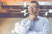 Handsome businessman in classic shirt and eyeglasses is holding a pencil, looking away and smiling while working in office