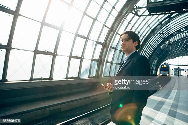 Schöner Businessoman stehen und warten auf ein train station Plattform