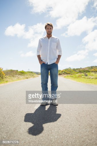 Handsome casual man standing on a road smiling at camera : Stock-Foto