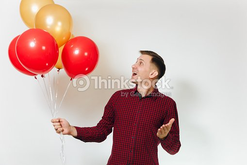 11a74f30 Handsome caucasian smiling fun young happy man 25-30 years in red plaid  shirt with yellow golden balloons, celebrating birthday, on white  background ...