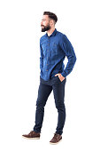 Handsome charming bearded business casual man with hands in pockets looking away and smile. Full body isolated on white.