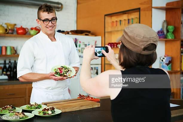 Bello Chef di cucina in cucina moderna pose per Smartphone fotografia