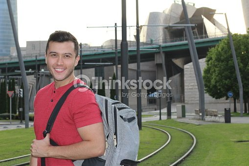 Handsome commuter smiling while waiting for train : Stock Photo