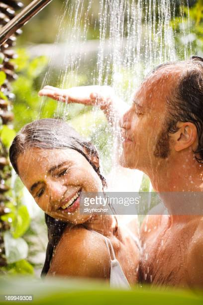 Handsome couple enjoying under shower in the exotic nature.