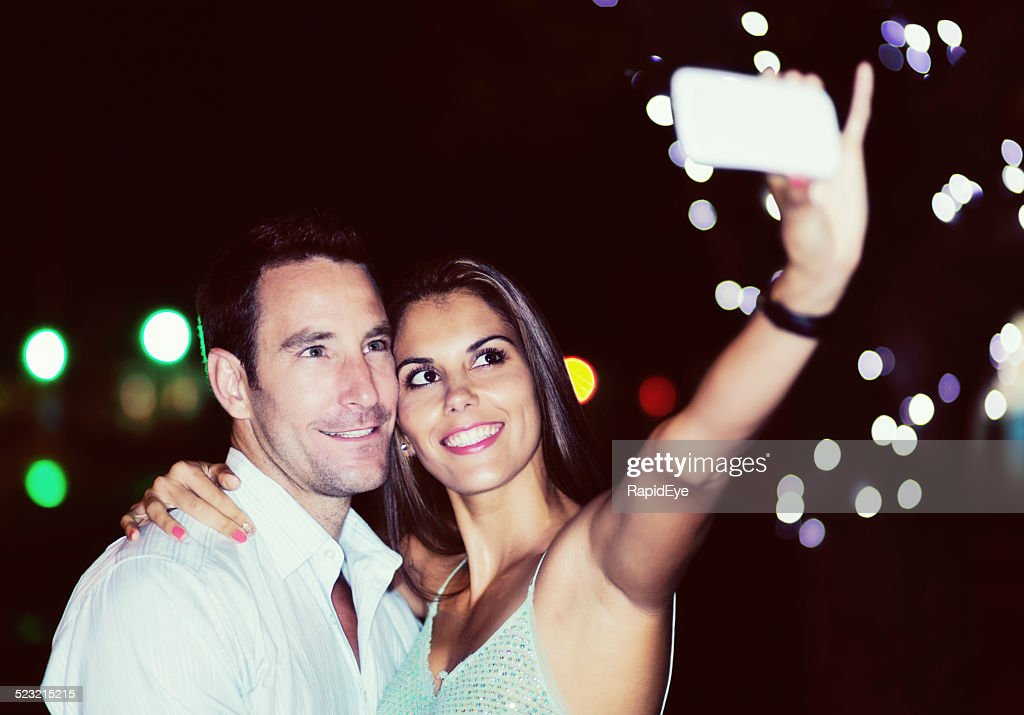 Handsome couple take happy selfie under twinkling lights