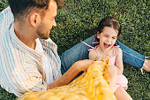 Handsome dad is spending time with his child sitting on the grass outdoors. Happy cute little girl playing with her father in the park. Happy father's Day. Daddy and daughter shares love