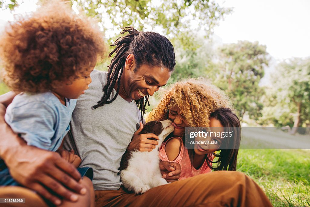 Handsome dad laughs as his beautiful wife gets puppy kisses. : Stock Photo