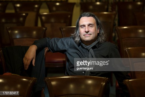 Handsome director is sitting in empty auditorium
