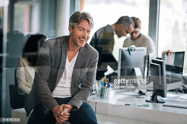Handsome executive sitting smilling through window