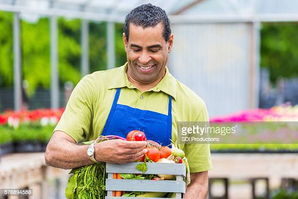 Handsome farmer looks at tomato at produce stand
