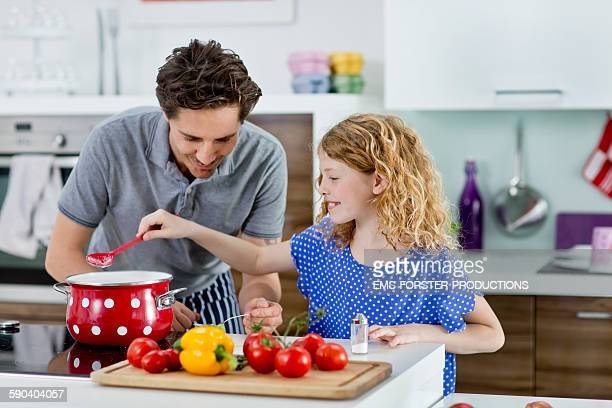 handsome father showing his daughter how to cook