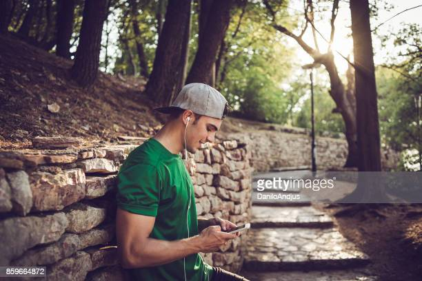 handsome fit man using his smartphone after workout in nature