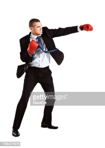 Handsome frowning businessman wearing boxing gloves is on the attack