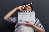 Beautiful young girl in casual clothes is covering her face with a clapperboard and looking at camera, standing against blackboard