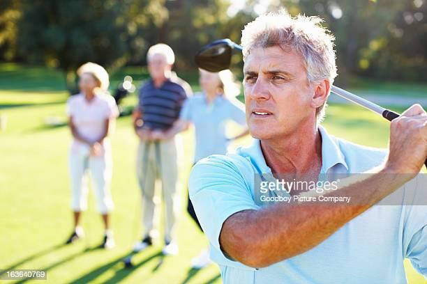 Handsome golfer swinging