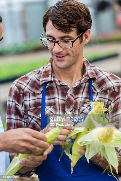 Handsome grocer looking at fresh corn with a customer