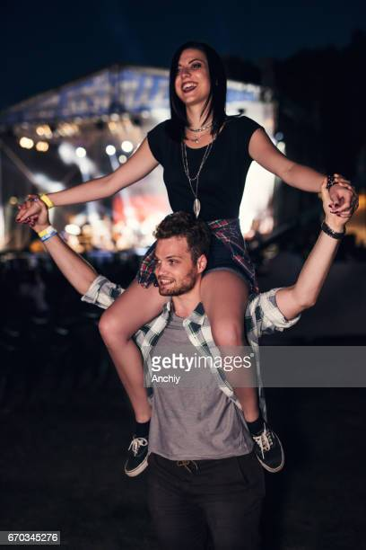 Handsome guy holding a cute girl friend on his shoulders. Stage glowing in the bakcground