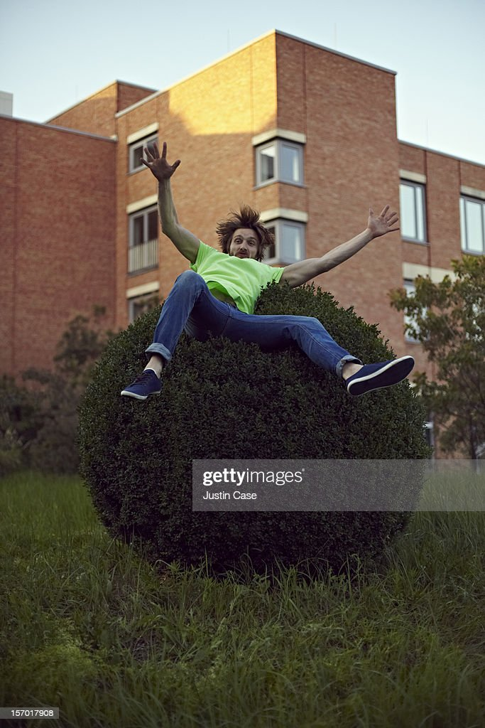 A handsome guy jumping on a bush : Stock Photo