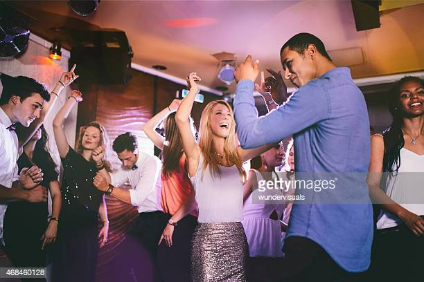 Handsome guy of African descent dancing with girlfriend in club