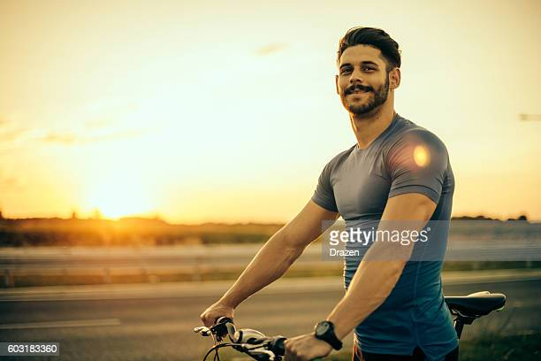 Handsome guy riding mountain bike in sunset