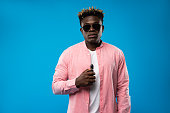 Need some relax. Waist up portrait of young man standing with vape device in hand. He is wearing pink shirt and sunglasses. Isolated on blue background
